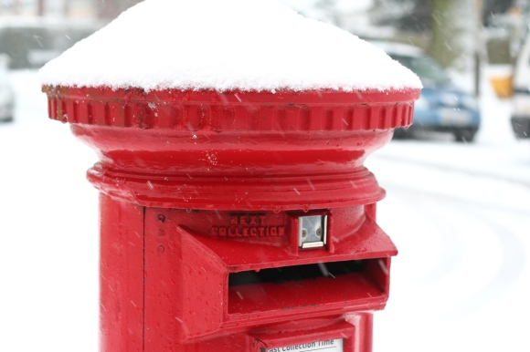 A red postbox in the snow